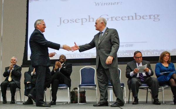 Joseph Greenberg, regional admissions director, shakes hands with University President Steven Knapp, right, at the Service Excellence Awards on Tuesday after receiving the Alumni Choice Award.