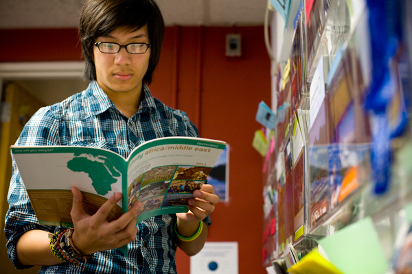 Junior Joel Uyenco flips through a brochure in the Office for Study Abroad, where he works as a peer counselor to help students decide where to study overseas. He traveled to Cape Town, South Africa last semester.