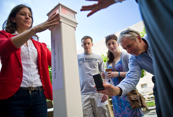 Freshman Hannah Spector, left, presents a lighthouse-shaped tool that changes color according to the level of carbon dioxide in the air, Friday in Kogan Plaza. Spector and her classmates created the device for an honors course taught by chemistry professor Houston Miller, right.