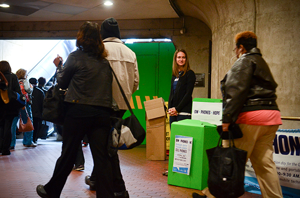Graduate student Brooke Stein waits inside the Foggy Bottom Metro station to collect used digital devices from commuters exiting the station. The University has been collecting used digital devices since October.