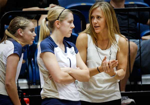 Head coach Amanda Ault, far right, talks to senior Christie Graf during last Wednesday's home opener. Ault has spoken about the increased difficulty of GW's schedule this season and said despite the team's record, the losses are providing opportunity for growth.