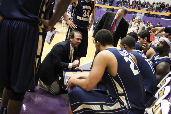 Head coach MIke Lonergan speaks with his team during a timeout earlier this season. Lonergan said that GW's inability to start the first half with an energetic push Tuesday ultimately kept it from making up the deficit.