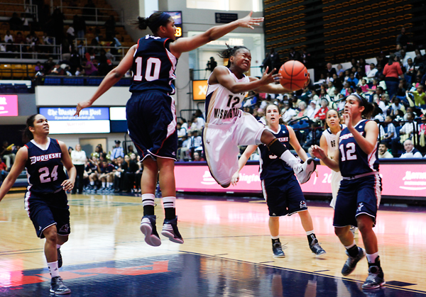 Senior guard Danni Jackson tries to get around a Duquesne defender while attempting a basket in Wednesday's game. Jackson had 17 points against the Dukes to go along with three assists.