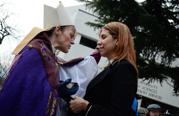 Bishop Mariann Edgar Budde from the Washington Episcopal Diocese places ashes on the forehead of a commuter Wednesday morning outside the Foggy Bottom Metro station.  Hundreds received ashes as part of the annual Catholic tradition that marks the beginning of Lent.  The principal church for the diocese, which spans 88 congregations in the Beltway area, is the Washington National Cathedral.