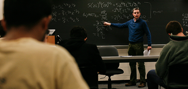 Tim Moore, an assistant economics professor, runs through microeconomic theory to his undergraduates. Enrollment has shot up 48 percent in some of the department's mid-level courses, testing professors' ability to work closely with students. The department has added six new economics professors this year.
