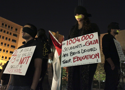 Students Marwane Moussaif and Dana Abu-Nasrah silently protested in Kogan Plaza on Tuesday night, advocating for the right to higher education for students on the Gaza Strip. Julie Bessler | Hatchet Photographer