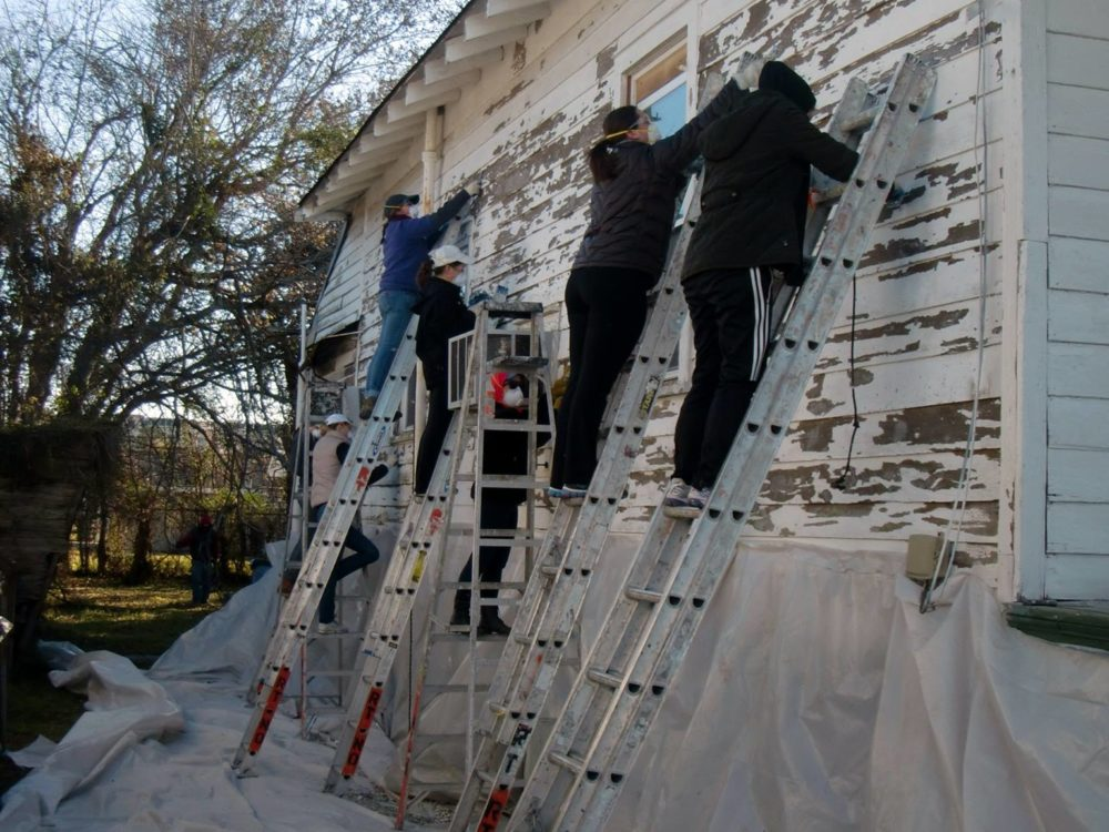 Students on ladders restore a home in New Orleans