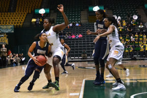 Then-junior guard Chakecia Miller squeezes pass a George Mason defender for a layup in a January game. File Photo by Aly Kruse | Hatchet Photographer