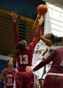 Freshman Caira Washington goes up for a shot over a Lady Hawk's defender Wednesday. Aly Kruse | Hatchet Photographer