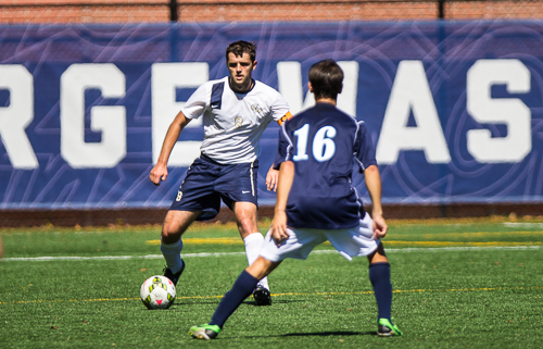 Senior defender Matthew Scott looks to pass the ball past a Saint Peter's player in a game earlier this season. Hatchet File Photo