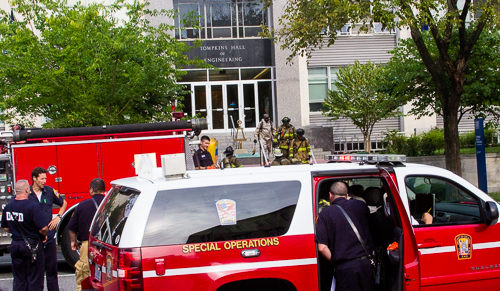 Firefighters, with some in hazmat suits, leave Tompkins Hall of Engineering. Zach Montellaro | Hatchet Staff Photographer