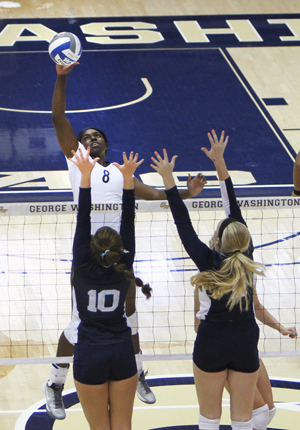Sophomore Chidima Osuchukwu hits the ball over Rhode Island defenders Friday night. Osuchukwu finished the match with 16 kills in the Colonials 3-2 win. Andrew Goodman | Hatchet Staff Photographer