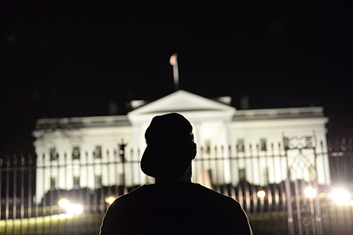 A peaceful protestor stands in front of the White House, while other protestors chanted and sang. Samuel Klein | Senior Photo Editor