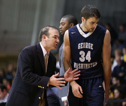 Head coach Mike Lonergan talks to his team alongside senior John Kopriva during GW's 63-50 loss at La Salle Saturday afternoon. Dan Rich | Hatchet Staff Photographer.