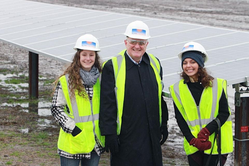 University President Steven Knapp poses with  Eleanor Davis and Zorah Roy at a solar power farm in North Carolina. Photo courtesy of GW Media Relations.