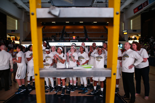 The Colonials wait to cut down the net to celebrate their title.