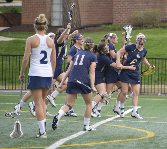 After sophomore Shea Cassidy scored the game-winning goal, teammates gathered around to celebrate the Colonials' come-from-behind, overtime victory on Friday. Andrew Goodman | Hatchet Staff Photographer