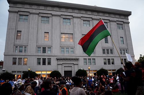 A Black Liberation flag, or Pan-African flag, waves over the crowd as the final words are delivered at the vigil.