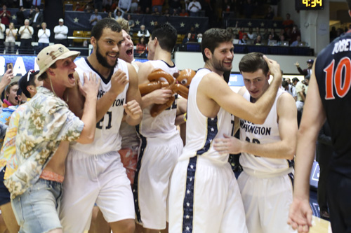 From left: Kevin Larsen, Patricio Garino and Matt Hart celebrate the Colonials' upset of No. 6 UVA. Garino and Larsen combined for 27 points. Dan Rich | Contributing Photo Editor