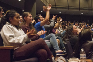 Students in the Dorothy Betts Marvin Theatre applaud the presidential candidates as they watch the debate on screen. Mike Shanahan | Hatchet Photographer